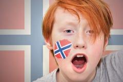 Muchacho de la fan del pelirrojo con la bandera noruega pintada en su cara Fotografía de archivo
