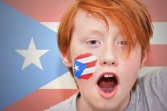 Muchacho de la fan del pelirrojo con la bandera puertorriqueña pintada en su cara Imágenes de archivo libres de regalías