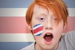 Muchacho de la fan del pelirrojo con la bandera rican de la costa pintada en su cara Imagen de archivo libre de regalías