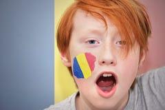 Muchacho de la fan del pelirrojo con la bandera rumana pintada en su cara Fotografía de archivo libre de regalías