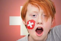 Muchacho de la fan del pelirrojo con la bandera suiza pintada en su cara Foto de archivo libre de regalías
