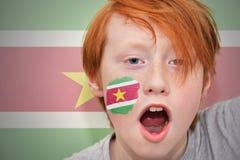 Muchacho de la fan del pelirrojo con la bandera surinamesa pintada en su cara Fotos de archivo libres de regalías