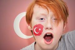 Muchacho de la fan del pelirrojo con la bandera turca pintada en su cara Imagenes de archivo