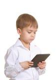 Muchacho de la lectura con el libro electrónico. Aislado Fotos de archivo libres de regalías