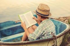 Muchacho de la lectura en barco viejo fotografía de archivo