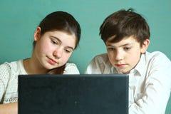 Muchacho de la muchacha con el ordenador portátil que estudia la lección en línea Fotos de archivo
