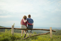Muchacho de la muchacha de la vista posterior que abraza paisaje Foto de archivo libre de regalías