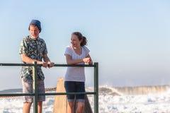 Muchacho de la muchacha de los adolescentes que habla olas oceánicas de marea de la piscina Imágenes de archivo libres de regalías