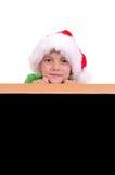 Muchacho de la Navidad ocultado detrás de muestra negra de la cartelera Fotos de archivo
