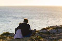 Muchacho de la niña y del adolescente abrazado en puesta del sol Fotos de archivo libres de regalías