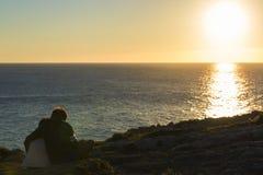 Muchacho de la niña y del adolescente abrazado en puesta del sol Imágenes de archivo libres de regalías