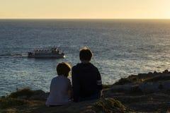 Muchacho de la niña y del adolescente en puesta del sol Imágenes de archivo libres de regalías