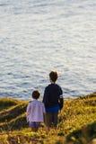 Muchacho de la niña y del adolescente en puesta del sol Foto de archivo libre de regalías