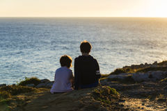 Muchacho de la niña y del adolescente en puesta del sol Fotografía de archivo