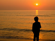 Muchacho de la silueta que se coloca en la playa Imagenes de archivo