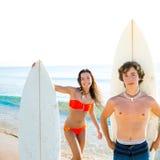Muchacho de las personas que practica surf y muchacha adolescente con la tabla hawaiana en playa Imágenes de archivo libres de regalías
