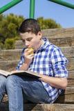Muchacho de Lifestyle.Young que lee un libro en escaleras de madera, verano Fotografía de archivo