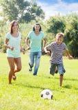 Muchacho de los pares y del adolescente que juega con el balón de fútbol Fotografía de archivo