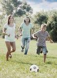 Muchacho de los pares y del adolescente que juega con el balón de fútbol Fotos de archivo libres de regalías