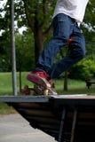 Muchacho de los tejanos que monta un monopatín en Skatepark en un medio tubo foto de archivo libre de regalías