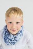 Muchacho de moda del adolescente en sonrisas azules de la bufanda Imagen de archivo