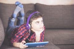 Muchacho de moda que escucha su música preferida usando su tableta Foto de archivo