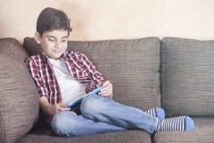 Muchacho de moda que usa el suyo tableta en casa Fotos de archivo
