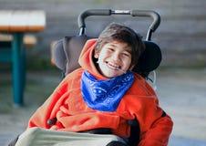 Muchacho de ocho años biracial hermoso, feliz que sonríe en wheelchai Fotos de archivo libres de regalías