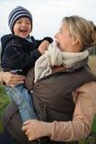 Muchacho de risa en el brazo de su madre Imagen de archivo
