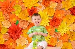 Muchacho de risa en fondo de las flores foto de archivo