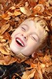 Muchacho de risa en una pila de hojas Fotografía de archivo libre de regalías
