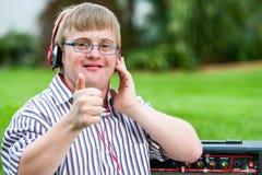 Muchacho de Síndrome de Down con las auriculares que hacen los pulgares para arriba Imagen de archivo