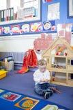 Muchacho de Síndrome de Down en el cuarto de niños Imagen de archivo