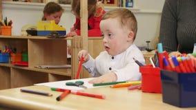 Muchacho de Síndrome de Down en el cuarto de niños
