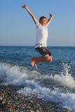 Muchacho de salto del adolescente en la costa de piedra Fotografía de archivo libre de regalías