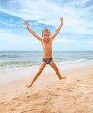 Muchacho de salto en la playa Foto de archivo libre de regalías