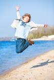 Muchacho de salto feliz en la playa imágenes de archivo libres de regalías
