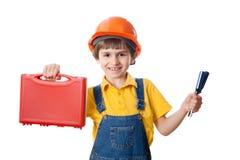 Muchacho de seis años feliz vestido como trabajador de construcción con el equipo de herramientas Fotos de archivo libres de regalías