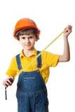 Muchacho de seis años vestido como trabajador de construcción con cinta métrica Imagen de archivo libre de regalías