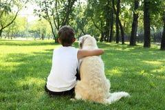 Muchacho de Tennager en el parque con un perro Fotografía de archivo
