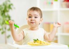 Muchacho de un año del niño en un highchair para alimentar Fotografía de archivo