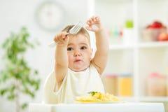 Muchacho de un año del niño en un highchair para alimentar Imagen de archivo libre de regalías