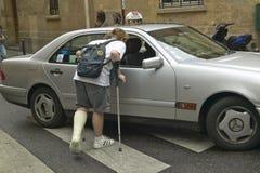 Muchacho de universidad con la pierna quebrada que señala por medio de una bandera abajo del taxi, París, Francia Fotografía de archivo libre de regalías