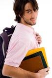 Muchacho de universidad sonriente que presenta con su bolso y libros Foto de archivo