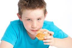 Muchacho de Youny que come un buñuelo azucarado. Foto de archivo