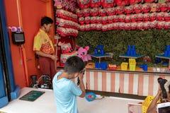 Muchacho de Ypung, lanzamientos no reconocibles en las latas en golpe de las cuentas del parque de atracciones Imagen de archivo libre de regalías