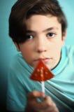 Muchacho del adolescente con el caramelo de azúcar de la forma de la sandía en el palillo Imagen de archivo libre de regalías