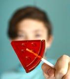 Muchacho del adolescente con el caramelo de azúcar de la forma de la sandía en el palillo Fotografía de archivo libre de regalías