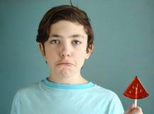 Muchacho del adolescente con el caramelo de azúcar de la forma de la sandía en el palillo Foto de archivo libre de regalías