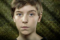 Muchacho del adolescente con el fondo verde asustadizo Foto de archivo libre de regalías